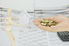 Man holding gold coins to buy house from wooden dummy Royalty Free Stock Photos