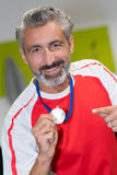 Man holding gold medal winner in competition. Man holding a gold medal winner in a competition Royalty Free Stock Image