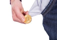 Man holding golden botcoin and showing his empty pocket. Isolated on white background Stock Photo
