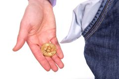 Man holding golden botcoin and showing his empty pocket. Isolated on white background Royalty Free Stock Image
