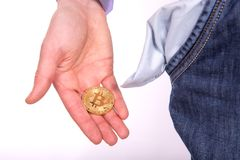 Man holding golden botcoin and showing his empty pocket. Isolated on white background Royalty Free Stock Photos