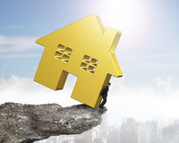 Man holding golden house on cliff edge Stock Photos