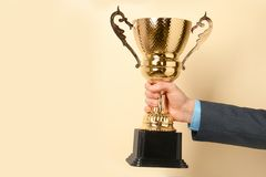 Man holding golden trophy cup on color background, closeup. Space for text royalty free stock photo