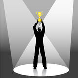 Man Holding Golen Trophy in a Spotlight. Illustration of a man holding up a gold trophy in the spotlights vector illustration