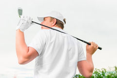 Man holding  golf club behind his back Stock Photography