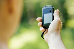 Man holding a GPS receiver and plan in his hand. Royalty Free Stock Photography