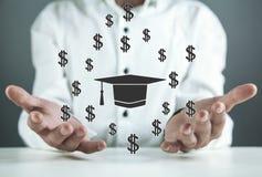 Man holding Graduation cap with dollar signs stock photos