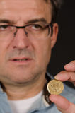 Man holding Greek drachma coin Stock Images