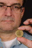 Man holding Greek drachma coin Royalty Free Stock Image