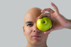 A man holding a green apple. And put it in his eye stock photos