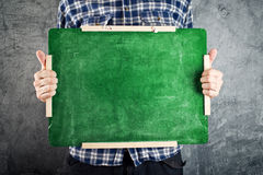 Man holding green chalkboard Stock Photography