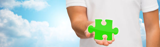 Man holding green puzzle over sky background Royalty Free Stock Photos