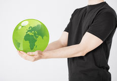 Man holding green sphere globe. Close up of man holding green sphere globe Royalty Free Stock Photos