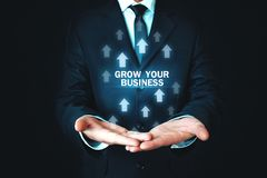 Man holding Grow Your Business words with growth arrows. royalty free stock photo