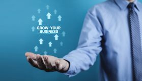 Man holding Grow Your Business words with growth arrows. royalty free stock image
