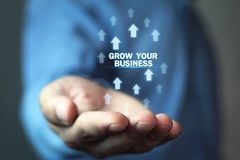 Man holding Grow Your Business words with growth arrows. stock images
