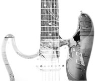 Man holding a guitar and guitar silhouette in double exposure in. Back view of a man holding a guitar and guitar silhouette in double exposure in black and white Royalty Free Stock Photography
