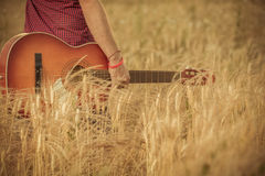 Man holding guitar and walking through wheat field Royalty Free Stock Image
