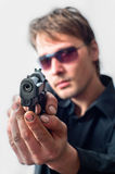 Man holding gun. With dirty hands with focus on pistol weraing sunglasses royalty free stock photo