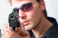 Man holding gun. With dirty hands with focus on pistol weraing sunglasses royalty free stock image