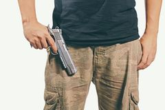 Man holding a gun. Man in a camouflage pants holding a gun isolated on white background, Army, Semi-automatic handgun, 45 pistol stock photos