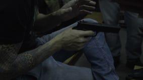 Man holding a gun in his hand. Men play weapon. Young man shooting perezarezhaet black metallic gun stock footage
