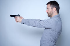 Man holding a gun in his hands Royalty Free Stock Photography