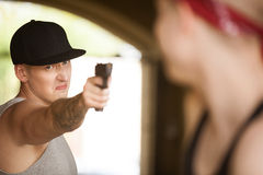 Man holding gun and pointing at person. Stock Image