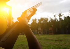 Man holding gun in street. Sunflare effect Stock Image