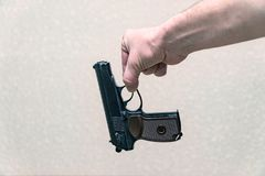 Man holding the gun with two fingers on a gray background. The man holding the gun with two fingers on a gray background. The gun is evidence royalty free stock image