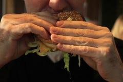 Man holding a hamburger Stock Photography