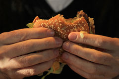 Man holding a hamburger Royalty Free Stock Photo
