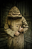 Man in raincoat holding hammer stock images