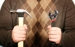 Man holding hammer and wrench. Man holding a hammer in his right hand and a wrench in his left hand while wearing a sweater Royalty Free Stock Photos