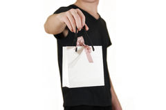 Man holding in hand blank white paper gift bag mock up. Empty pa Royalty Free Stock Photo