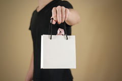 Man holding in hand blank white paper gift bag mock up. Empty pa Stock Photos
