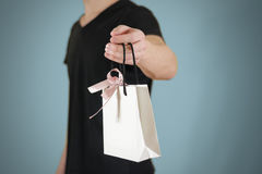 Man holding in hand blank white paper gift bag mock up. Empty pa Royalty Free Stock Images