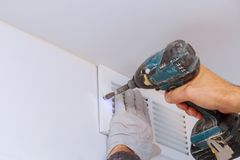 Man is holding hand drill in hands. Worker installing the wall bathroom vent works renovation in the flat. Man is holding hand drill in hands. Worker installing royalty free stock photos