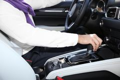 Man holding hand on gear lever in modern car,. Closeup stock photography