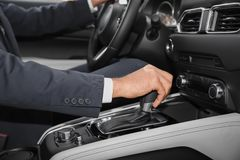 Man holding hand on gear lever in modern car. Closeup royalty free stock photos