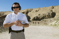 Man Holding Hand Gun At Firing Range. Portrait of a men holding handgun at shooting range with mountains in the background Royalty Free Stock Photography