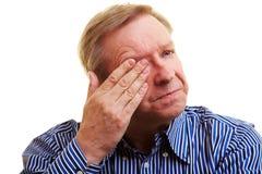 Man holding hand over his eye. Elderly man holding hand over his aching eye Royalty Free Stock Photos