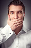 Man holding hand over his mouth Stock Photography
