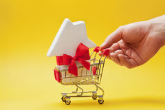 Man holding hand shopping cart with house decorated ribbon on yellow background. Buying a new home, gift or sale of real estate. stock photography