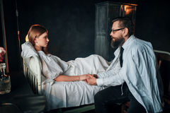 Man holding a hand of sick loved woman in bed Royalty Free Stock Photography
