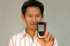 Man holding the handphone. Man showing the handphone screen - focus on both face and handphone Stock Image