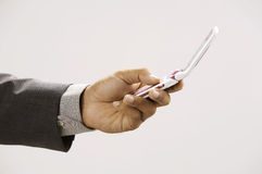 Man holding a handphone. Man holding a hand phone checking massages Royalty Free Stock Photo