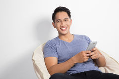 Man holding a handphone while sitting on the chair Royalty Free Stock Images
