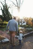 Man Holding Hands With Baby While Walking Through Pathway Facing Sunlight Royalty Free Stock Images