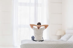Man holding hands behind head while sitting on bed in the morning Stock Photo